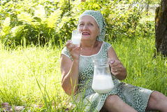Seniors female drinks fresh milk Stock Photo