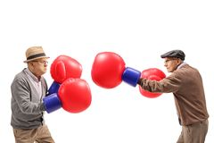 Seniors fighting each other with big boxing gloves stock photography