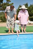 Seniors with girl near a pool Stock Image
