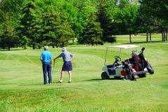 Seniors golfing. Two senior men on golf course Royalty Free Stock Photography