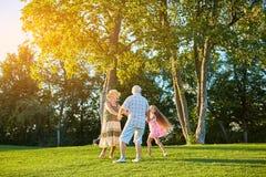 Seniors with grandchild, roundelay. Royalty Free Stock Images