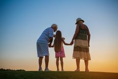 Seniors with grandchild, sunset. Seniors with grandchild sunset. Girl and grandparents, evening sky royalty free stock photography