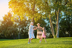 Seniors with granddaughter, roundelay. Seniors with granddaughter roundelay. Cheerful people dancing outdoors Stock Photography