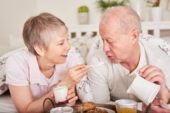 Seniors have breakfast in bed Royalty Free Stock Photography