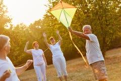 Seniors having fun whith kite flying Royalty Free Stock Photos