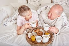 Seniors having room service breakfast. In their bedroom Stock Photography