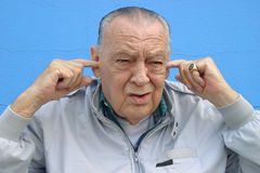 Seniors,Hearing loss. Man with fingers in his ears with a curious expression on his face. Hearing loss Bad news Noise pollution stock image