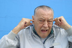 Seniors, Hearing loss anxiety. Man with fingers in ears while shouting. . Bad news, emotional stress,Hearing loss with frustration.,Humourous Caricature stock image