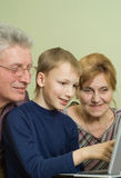 Seniors with her grandson play in a notebook Royalty Free Stock Photo
