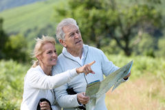 Seniors hikers searching for the hiking way in mountains with map. Senior hikers reading orientation map stock image