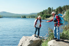 Seniors hiking. Mature men helping his wife walk on stone during trip in the country stock photo