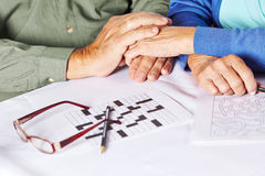 Seniors holding hands in nursing. Two seniors holding their hands in a nursing home with riddles and glasses on table Stock Photos