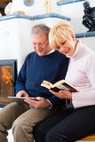 Seniors at home in front of fireplace Stock Image
