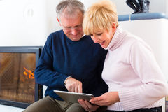 Seniors at home in front of fireplace. Quality of life - two elderly people sitting at home in front of the furnace, writing emails on the tablet computer Royalty Free Stock Images