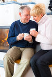 Seniors at home in front of fireplace. With tea cup Royalty Free Stock Photography