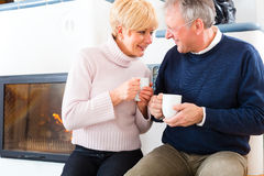 Seniors at home in front of fireplace. With tea cup Royalty Free Stock Photos