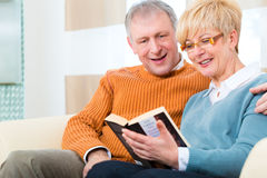 Seniors at home reading a book together. Quality of life - two elderly people sitting at home on the couch, he embraces his wife Stock Photography