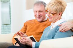 Seniors at home reading a book together Stock Photo