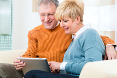 Seniors at home with tablet computer Stock Photos
