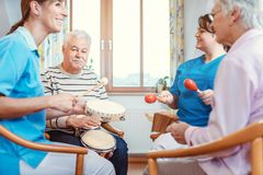 Free Seniors In Nursing Home Making Music With Rhythm Instruments Stock Photography - 161715102