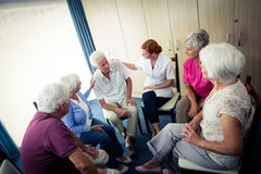 Seniors interacting with nurse. In the retirement house Stock Photo