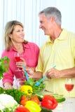 Seniors at kitchen. Happy seniors couple cooking at kitchen stock image