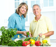 Seniors at kitchen. Happy seniors couple cooking at kitchen Stock Images
