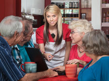 Seniors with Laptop and Helpful Waitress Royalty Free Stock Photos