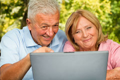 Seniors Laptop. Senior couple browsing on laptop outdoors. Positive expression Stock Photography
