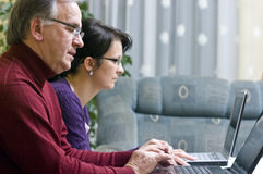 Seniors with laptops. Two seniors (father with his adult daughter) working on laptops Royalty Free Stock Images