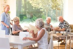 Seniors in living room. Group of seniors spending free time in bright living room with big window at nursing house royalty free stock image