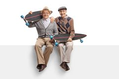 Seniors with longboards sitting on a panel Stock Photography