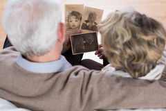 Seniors looking at old pictures. Senior couple looking at old pictures from childhood Stock Images
