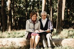 Happy senior couple looking at photos outdoors royalty free stock photos