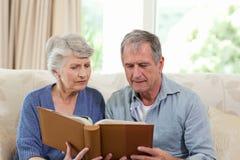 Seniors looking at their photo album Stock Photo