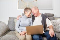 Seniors in love hug on the couch. Happy seniors in love hug on the couch holding laptop Royalty Free Stock Image