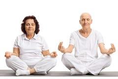 Seniors meditating on an exercise mat. Isolated on white background Stock Photo