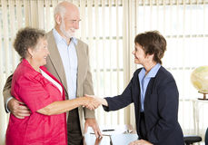Seniors Meeting Financial Advisor. Senior couple meets with a friendly financial adviser Stock Photography