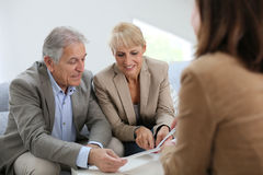 Seniors meeting realtor reading contract. Senior couple meeting real estate agent Royalty Free Stock Photo