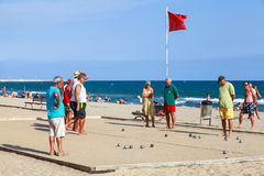 Seniors men play Bocce on sandy beach in Spain Royalty Free Stock Photo