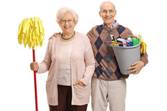 Seniors with a mop and cleaning products. Seniors with a mop and a bucket filled with cleaning products looking at the camera and smiling isolated on white royalty free stock image