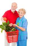 Seniors with Organic Produce. Healthy senior couple shopping for organic produce.  Isolated on white Stock Image