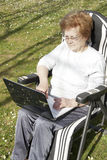 Seniors people with technology. Senior woman with computer outdoors Stock Images