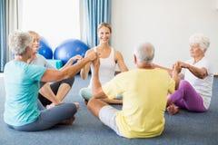 Seniors performing yoga. During sports class Royalty Free Stock Photos