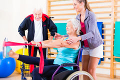 Seniors in physical rehabilitation therapy. With trainer stock image