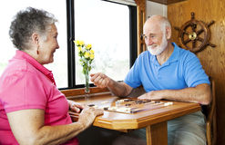 Seniors Play Backgammon. Senior couple playing backgammon in the kitchen of their motor home Stock Photo