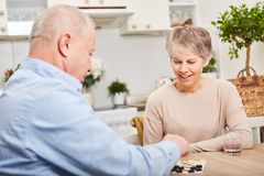 Seniors play board game for leisure. And relaxation as couple in retirement activity Stock Photo