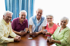 Seniors playing cards together. In a retirement home Stock Photos