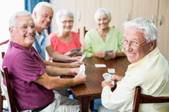 Seniors playing cards together Stock Photos