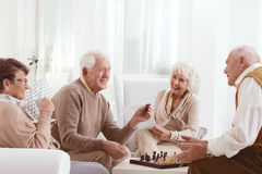 Seniors playing chess. Group of happy seniors playing chess together Royalty Free Stock Photography
